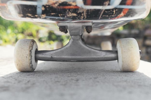 日光の下で地面にスケートボードのクローズアップ