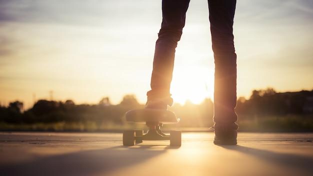 日没時に日光の下で木々に囲まれたスケートボーダーのクローズアップ