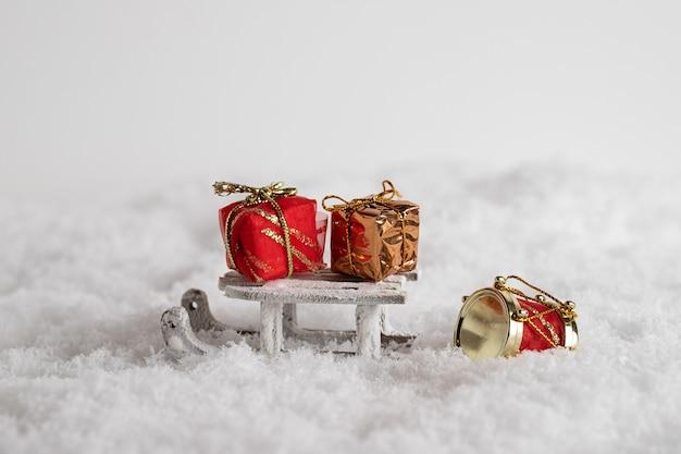 雪の中のそりとカラフルなギフトボックスのクローズアップ、白い背景のクリスマスのおもちゃ