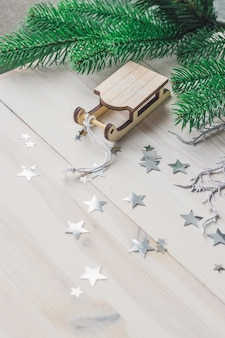ライトの下のテーブルに小さな木製そり飾りのクローズアップ