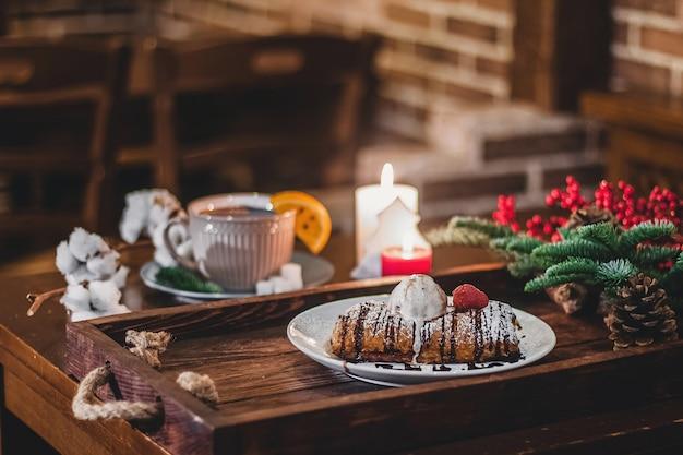 竹の枝の近くのクリスマスプレートにイチゴとシュトルーデルのクローズアップ。