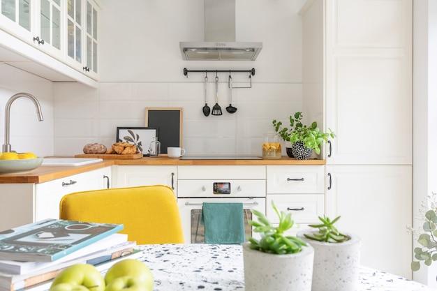 明るいキッチンのインテリアの実際の写真の果樹や雑誌のテーブルのクローズアップ