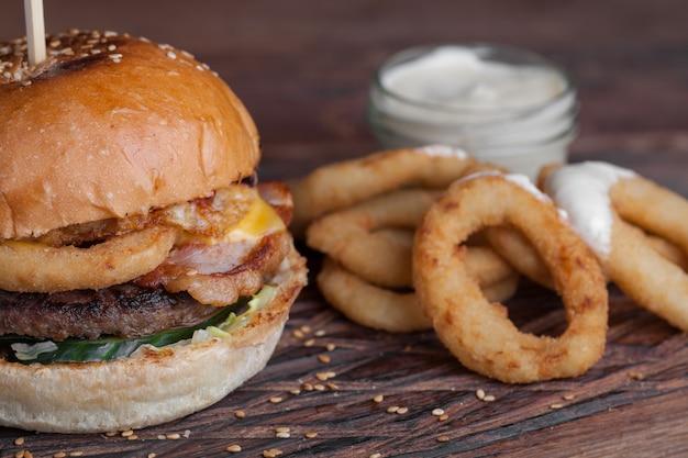 Крупный план вкусного бургера с закусками.