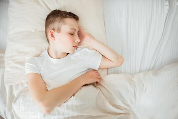 ベッドで寝ている10代の少年のクローズアップ