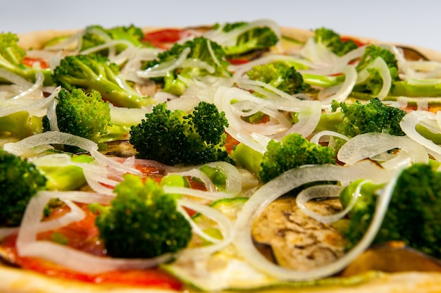 ベジタリアンピザのクローズアップ。トマトソース、ブロッコリー、トマト、ズッキーニ、ナス、オニオンリングのブラジル風ピザ。セレクティブフォーカス