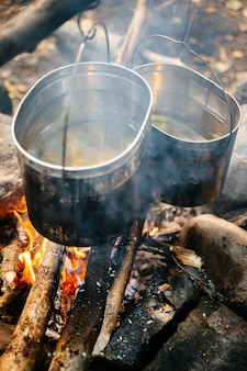 Крупным планом вертикальная алюминиевая посуда в саже над костром для приготовления супа в поле
