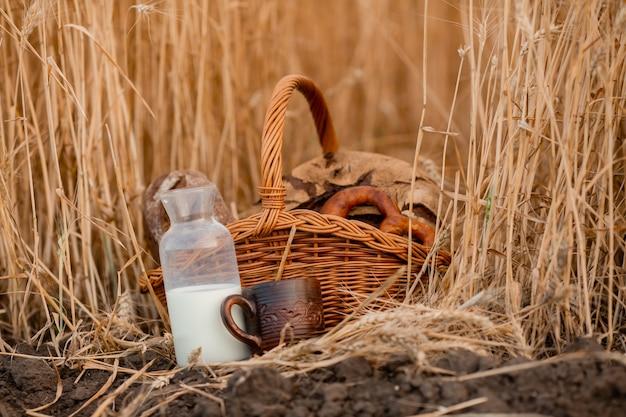 地面に立っているボトルのパン、マグカップ、ミルクと籐のバスケットのクローズアップ