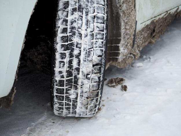 雪と氷と冬の車のタイヤのトレッドのクローズアップ