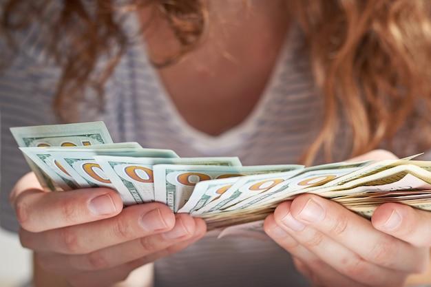 Крупным планом руки женщины считают нас деньги доллар