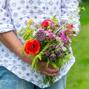 緑の草の上に立っている間、さまざまな色とりどりの花の花束を保持している女性のクローズアップ