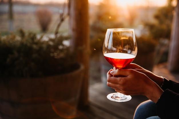 テラスで夕日の光の中で赤ワインのグラスを保持している女性のクローズアップ