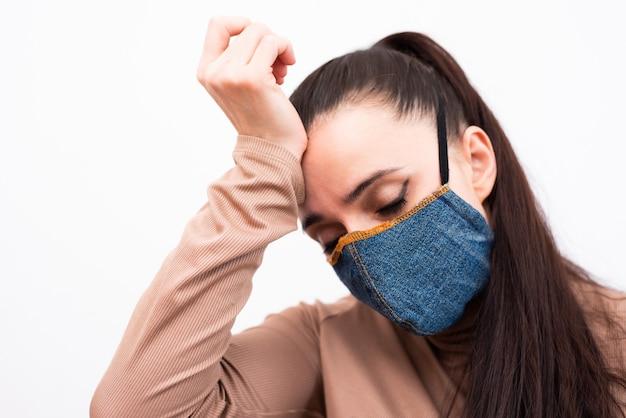 保護デニムマスクの女性のクローズアップ。世界的な大流行時のコロナウイルスとコビッド-19の予防