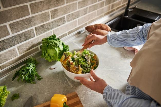 キッチンでビーガンサラダを準備しているヒジャーブの女性のクローズアップ。
