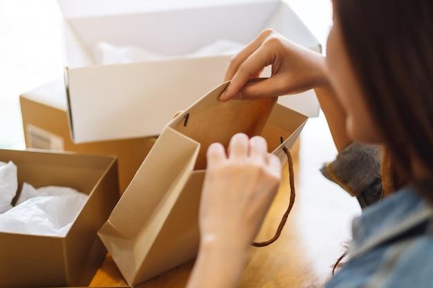 Крупный план женщины раскрывая и смотря внутреннюю хозяйственную сумку дома для поставки и концепции покупок онлайн