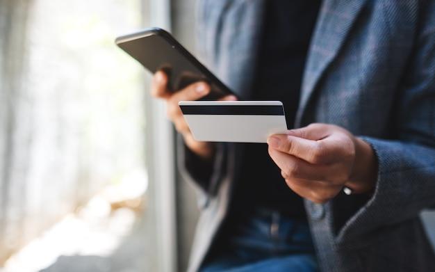 Макрофотография женщины с помощью кредитной карты для покупки и покупки онлайн на мобильном телефоне