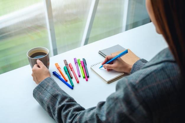 テーブルの上の色のペンとコーヒーカップでコーヒーを飲みながら空白のノートに書く女性のクローズアップ