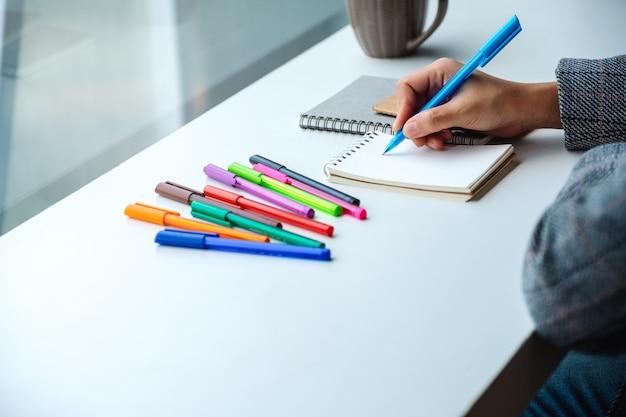 テーブルの上の色のペンとコーヒーカップで空白のノートブックに書く女性のクローズアップ