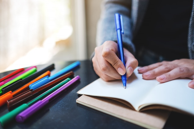 テーブルの上の色のペンで空白のノートに書く女性のクローズアップ