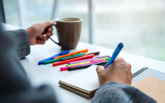 コーヒーを飲みながら色のペンで空白のノートに書く女性のクローズアップ