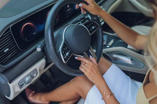 Крупным планом руки женщины на рулевом колесе в современном автомобиле