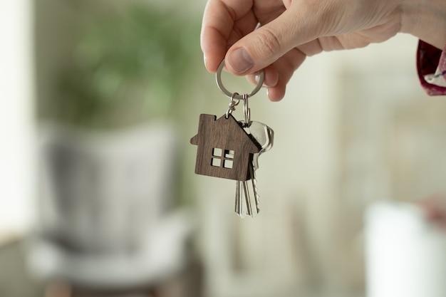 Крупным планом руки женщины держат ключи от нового дома женщина переезжает в новую квартиру