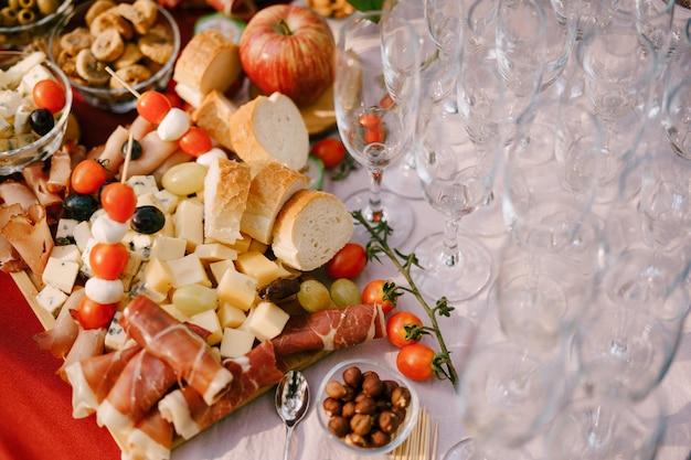 Крупным планом деревянная разделочная доска с мясным ассорти, сыром и хлебом на столе деликатесов