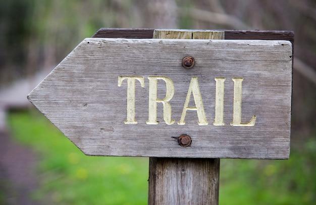 그것에 쓰여진 [trail] 단어로 나무 간판의 근접 촬영