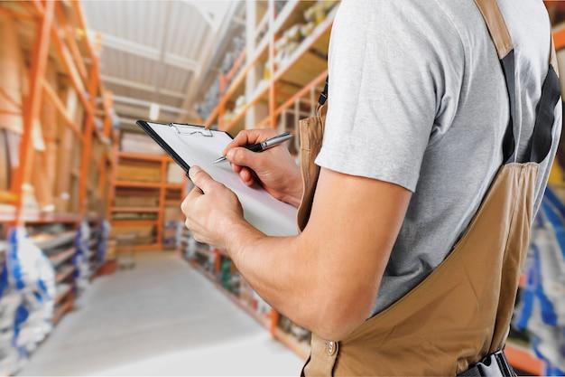 Крупным планом работника со списком, проверяющим состояние запасов