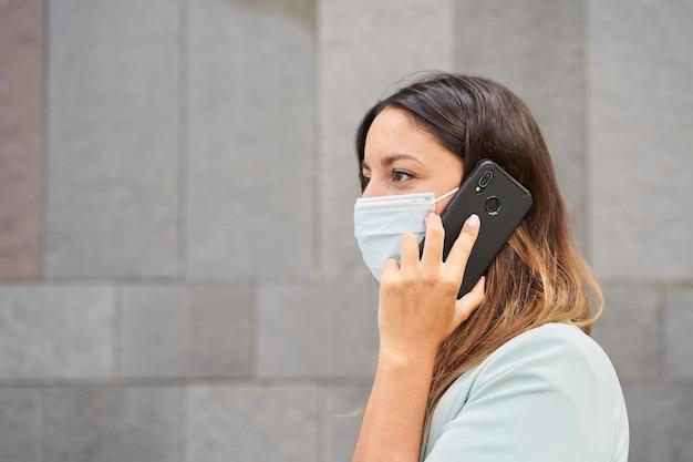 Крупным планом работающая женщина с лицевой маской разговаривает по телефону. слева есть пустое место для вставки текста. фон - серая стена.