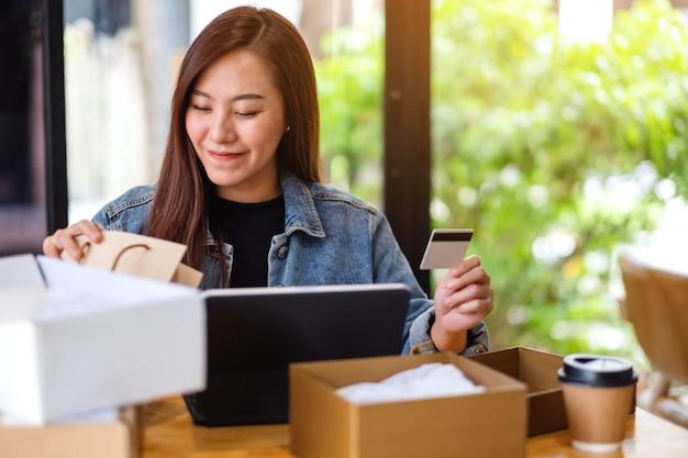 Крупный план молодой азиатской женщины используя пк таблетки и кредитную карточку для покупок онлайн с коробкой почтовой посылки и хозяйственными сумками на таблице