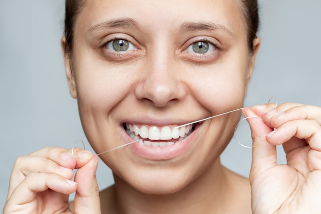 Крупным планом молодая красивая кавказская женщина чистит зубы зубной нитью гигиена полости рта, стоматологическая помощь