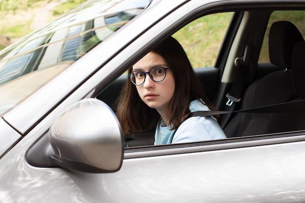 어린 소녀 드라이버의 근접 촬영입니다. 소녀는 차를 운전하는 법을 배웁니다. 교통 체증, 교통 체증에 대한 두려움. 자동차 운전으로 인한 스트레스.