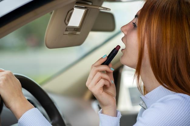 차량의 운전대 뒤에 있는 자동차 백미러를 보고 어두운 빨간 립스틱으로 화장을 수정하는 젊은 빨간 머리 여성 운전자의 클로즈업.