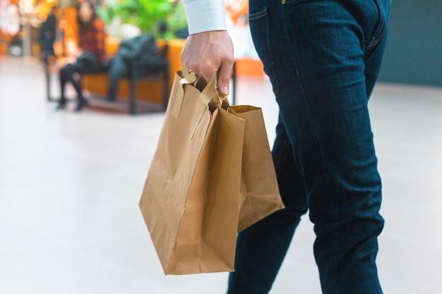 Крупный план молодого стильного человека, идущего в торговом центре с экологически чистыми хозяйственными сумками в руке с товарами и одеждой. продажи, скидка распродана концепция. сезонные распродажи.