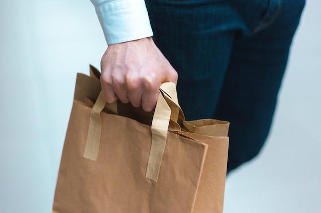 エコロジーにやさしい買い物袋を手に商品や服を持ってモールを歩いている若いスタイリッシュな男のクローズアップ。販売、割引完売コンセプト。季節限定完売。