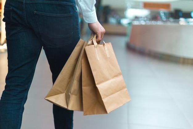상품과 옷을 손에 들고 친환경적인 쇼핑백을 들고 쇼핑몰을 걷고 있는 세련된 젊은이의 클로즈업. 판매, 할인 매진 개념입니다. 시즌 품절.