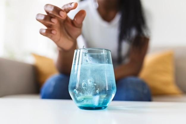 Крупным планом молодая женщина роняет шипучий антацид в стакан с водой. молодая женщина с трудом положила растворимую таблетку с лекарством от боли или похмелья в стакан воды