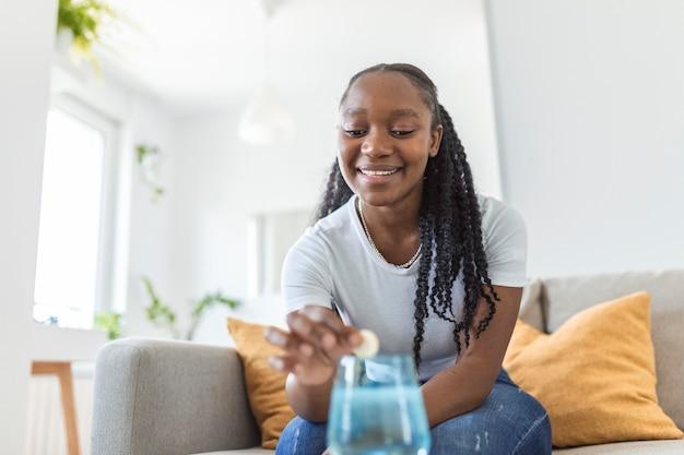 コップ一杯の水に発泡性制酸剤を落とす若い女性のクローズアップ。若い女性は、痛みや二日酔いの薬が入った可溶性の錠剤をコップ一杯の水に入れることはほとんどありません