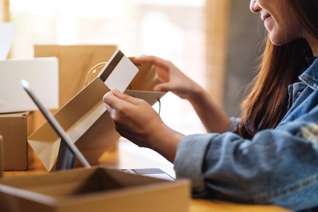 Крупным планом молодой женщины с помощью планшетного пк и кредитной карты для покупок в интернете, открытия сумок и почтовых посылок на столе