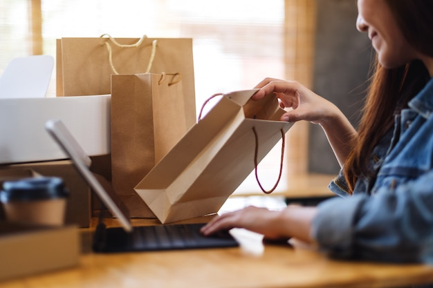 オンラインショッピングにタブレットpcを使用して、テーブルの上に買い物袋と郵便小包を開く若い女性のクローズアップ