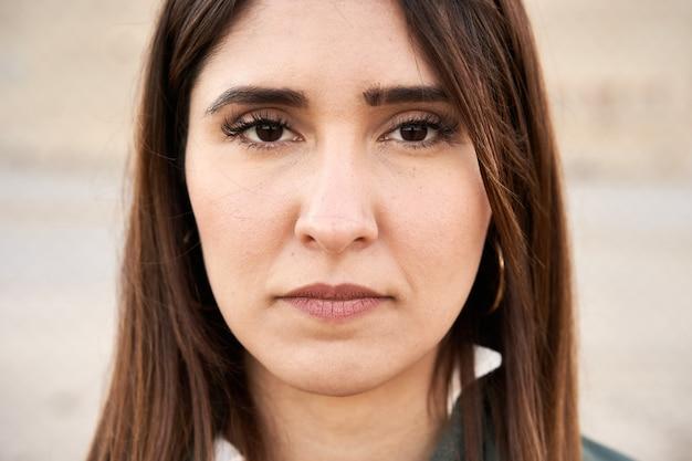 彼女の顔に真剣な表情でカメラを見ている暗い目を持つ若い女性のクローズアップ