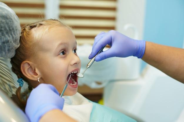 입을 벌리고 있는 사랑스러운 여자 아기의 클로즈업, 조기 충치 진단 및 치아 질병 예방을 위해 정기적으로 치과를 방문하는 동안 치과 사무실의 의자에 앉아