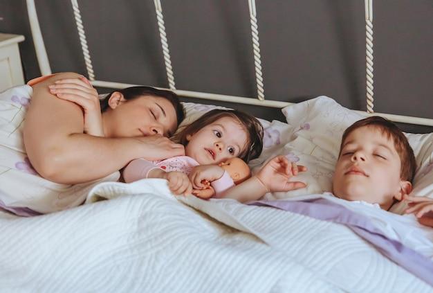 リラックスした朝に眠っている彼女の家族と一緒にベッドの上に横たわっている人形を抱きしめる愛らしい少女のクローズアップ。週末の家族の余暇の時間の概念。