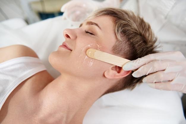 Крупный план руки косметолога, использующей деревянный шпатель для нанесения прозрачного анестезирующего геля на лицо женщины, чтобы сделать процедуру лазерной эпиляции безболезненной.
