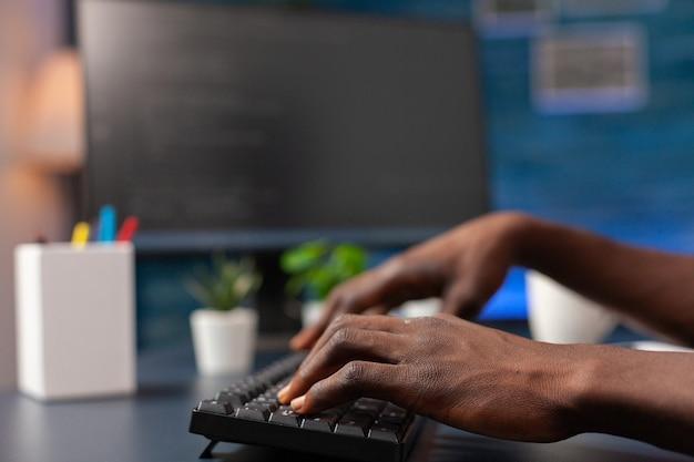 アフリカ系アメリカ人の従業員の手プログラミングバイナリコードのクローズアップ