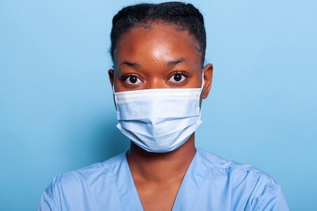 感染を防ぐために医療用フェイスマスクを身に着けているアフリカ系アメリカ人の開業医の看護師のクローズアップ