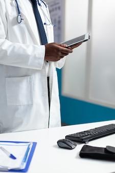 タブレットコンピューターを保持しているアフリカ系アメリカ人の専門医のクローズアップ