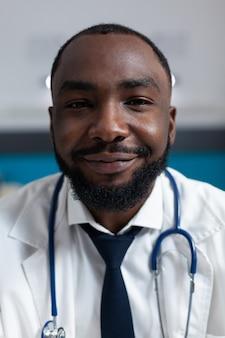 카메라를 보고 청진기를 가진 아프리카계 미국인 치료사 의사의 근접 촬영