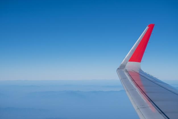 Крупный план крыла самолета с голубым небом и видом на горный пейзаж.