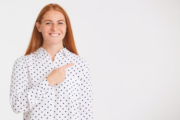 長い赤い髪とそばかすのある驚くべき素敵な若い女性のクローズアップは水玉シャツを着ています